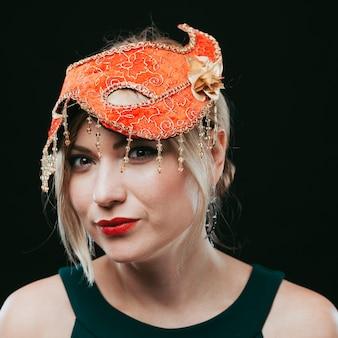 Mujer rubia en máscara de carnaval naranja