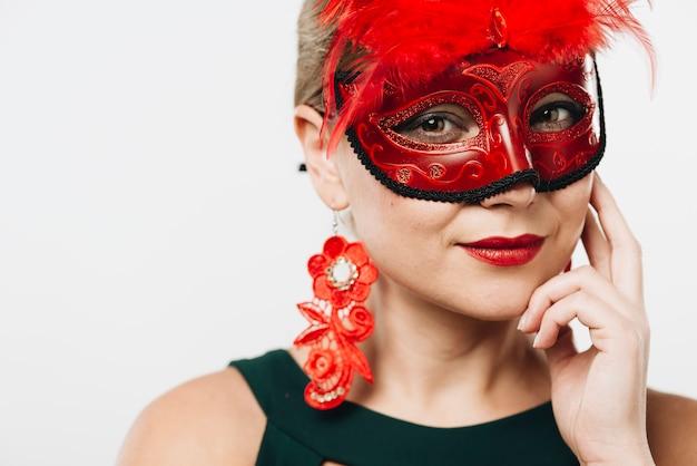 Mujer rubia en máscara de carnaval rojo