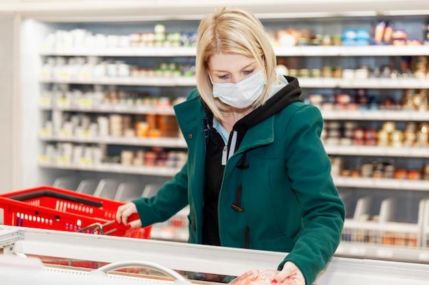 Mujer rubia con una máscara médica está de compras en el supermercado. autoaislamiento en una pandemia.