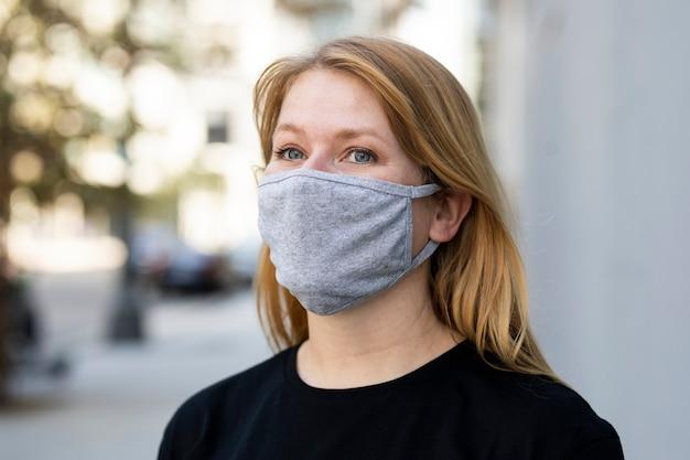 Mujer rubia con máscara en la sesión de fotos al aire libre de la ciudad