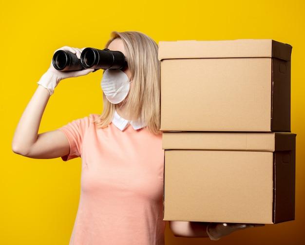 Mujer rubia en mascarilla con cajas de entrega y binoculares en pared amarilla