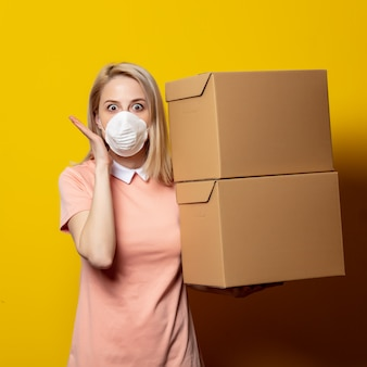 Mujer rubia en mascarilla con cajas de entrega en la pared amarilla