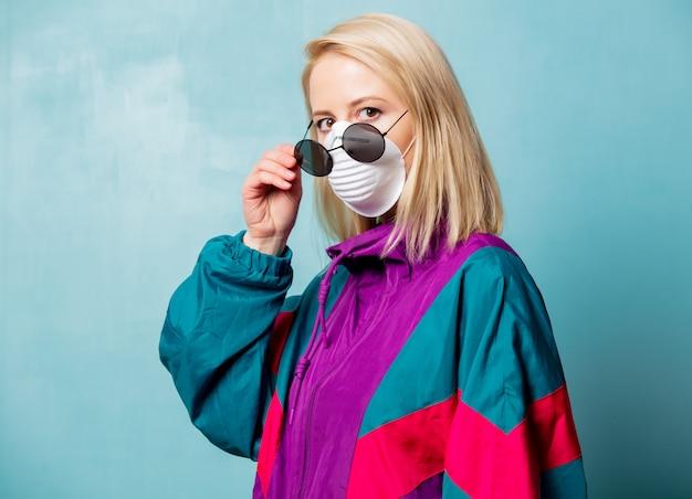 Mujer rubia en mascarilla y ropa estilo años 90