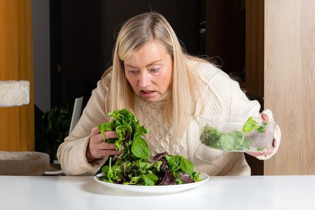 Mujer rubia de mediana edad con expresión facial insatisfecha preparando ensalada verde en la cocina, alimentación saludable y concepto de dieta