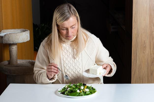 Mujer rubia de mediana edad preparando ensalada verde en la cocina, alimentación saludable y concepto de dieta