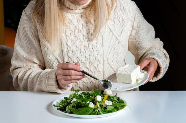 Mujer rubia de mediana edad preparando ensalada verde en la cocina, concepto de alimentación y dieta saludable, primer plano