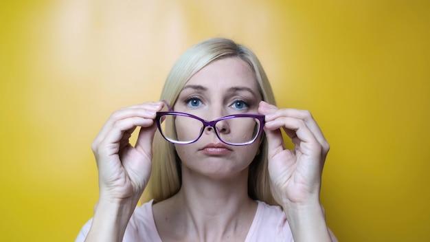 Una mujer rubia de mediana edad que se pone elegantes gafas de moda y sonríe, miopía, astigmatismo y enfermedades oftalmológicas.