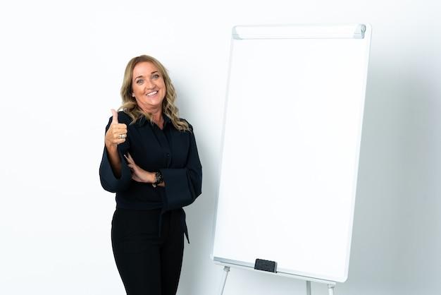 Mujer rubia de mediana edad sobre blanco aislado dando una presentación en la pizarra y con los pulgares hacia arriba
