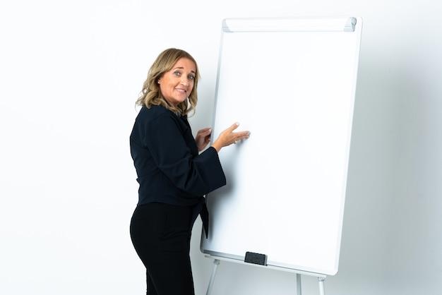 Mujer rubia de mediana edad sobre fondo blanco aislado dando una presentación en la pizarra