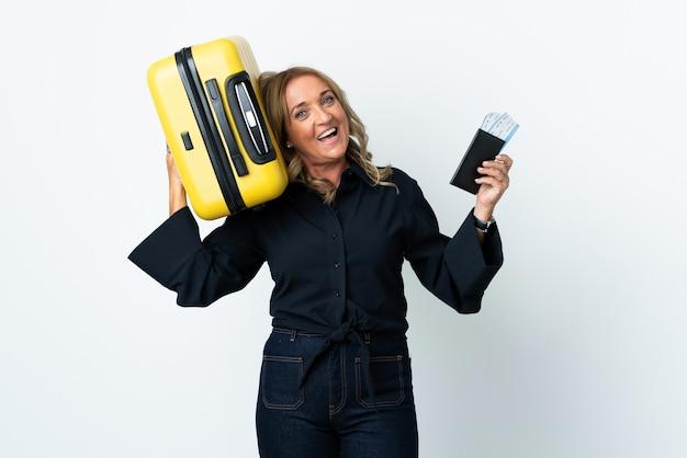 Mujer rubia de mediana edad sobre fondo blanco aislado en vacaciones con maleta y pasaporte