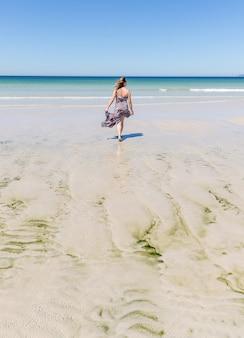 Mujer rubia de mediana edad con un vestido caminando por la playa