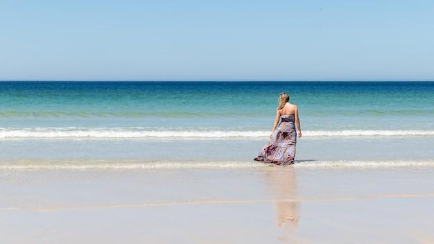 Mujer rubia de mediana edad con un vestido se relaja en la playa
