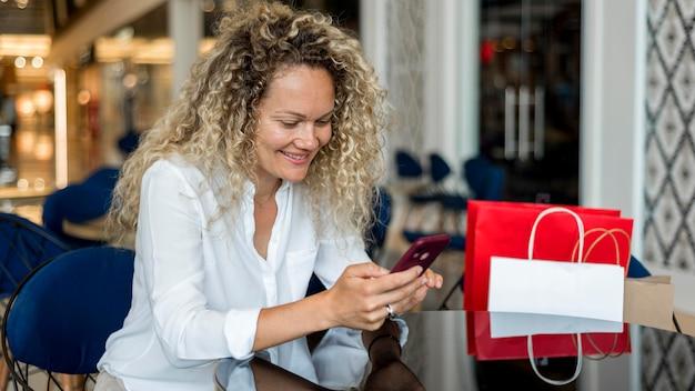 Mujer rubia con mensajes de texto de pelo rizado