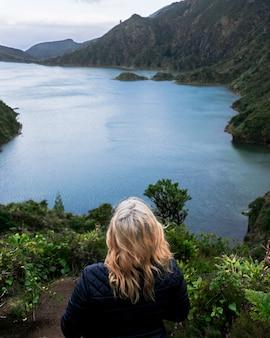 Una mujer rubia mira hacia un gran lago en azores