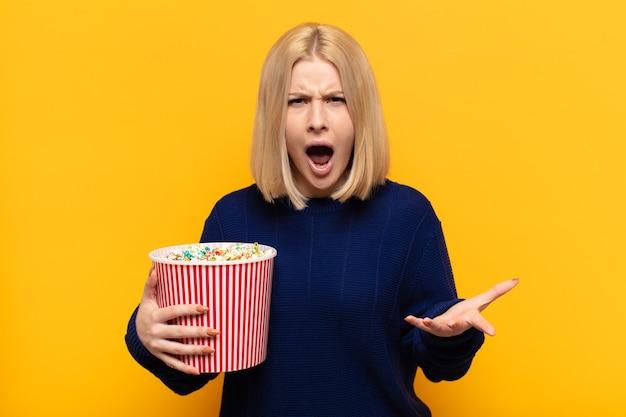 Mujer rubia mirando enojado, molesto y frustrado gritando wtf
