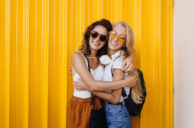 Mujer rubia de moda en auriculares posando con una amiga morena sobre fondo amarillo.