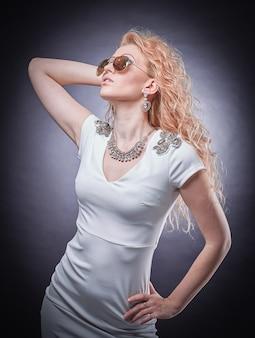 Mujer rubia de moda en gafas de sol. aislado en un fondo oscuro.