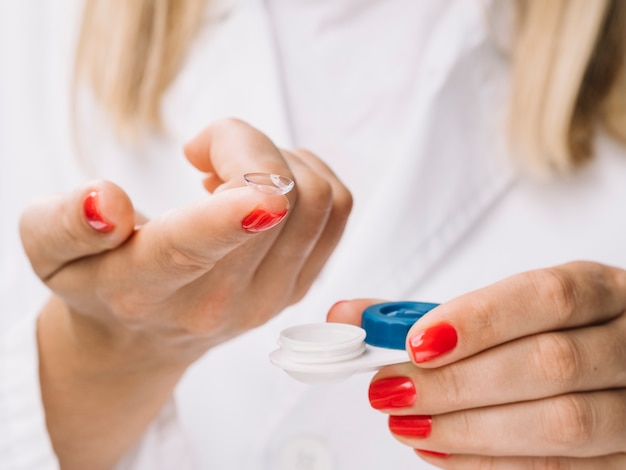 Mujer rubia mostrando a la cámara lentes de contacto