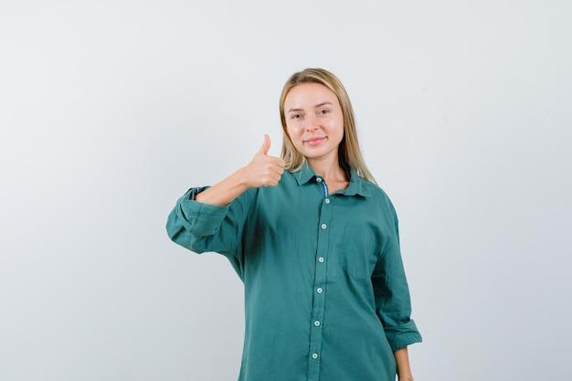 Mujer rubia mostrando el pulgar hacia arriba en camisa verde y mirando alegre.