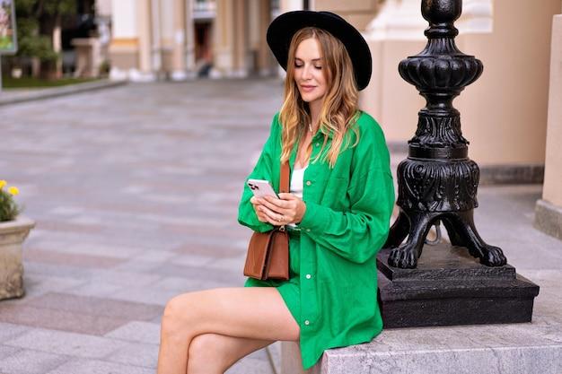 Mujer rubia muy elegante posando en el casco antiguo de la ciudad europea, sosteniendo su teléfono