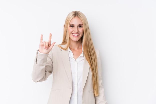 La mujer rubia del negocio joven en la pared blanca que muestra un cuernos gesticula como concepto de la revolución.