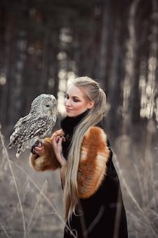 Mujer rubia en otoño en abrigo de piel con búho en mano primera nieve