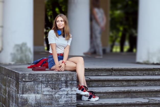 Mujer rubia en pabellón de jardín. atractiva mujer caucásica de unos 25 años en tela de moda con zapatos de plataforma y pantalones cortos está sentada en las escaleras en el parque público.