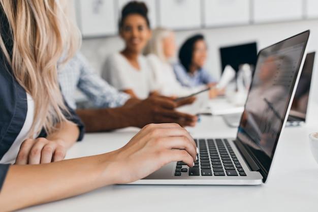 Mujer rubia con peinado elegante escribiendo texto en el teclado en la oficina. retrato interior de empleados internacionales con secretaria usando laptop.