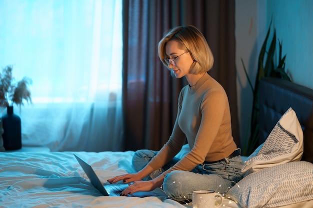 Mujer rubia de pelo corto en la cama blanca en jeans con una computadora portátil.