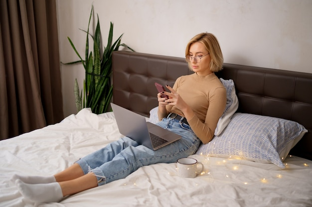 Mujer rubia de pelo corto en la cama blanca en jeans con un ordenador portátil con smartphone.