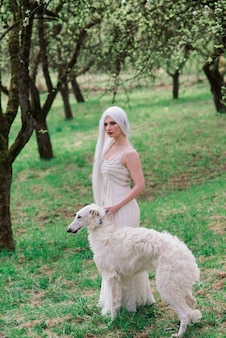 Mujer rubia de pelo largo jugando con su perro lobo ruso en el jardín