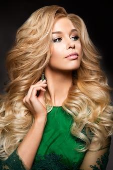 Mujer rubia con pelo largo y rizado y maquillaje glamour.