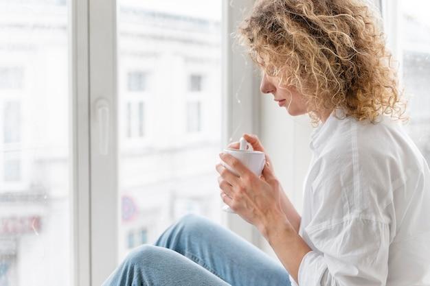 Mujer rubia de pelo rizado relajándose en casa cerca de la ventana