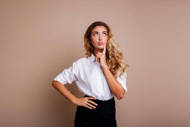 Mujer rubia pensativa que presenta el aislante en la pared beige. ropa de trabajo casual con estilo.