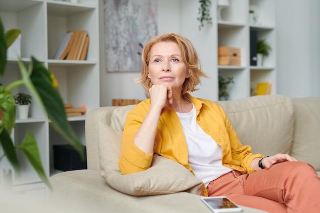 Mujer rubia pensativa relajándose en el sofá en el hogar mientras disfruta de un descanso en medio de la jornada laboral durante la cuarentena