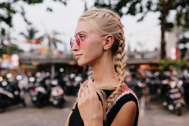 Mujer rubia pensativa en traje negro posando sobre fondo de calle borroso. dama bronceada con trenzas lleva gafas de sol rosas.