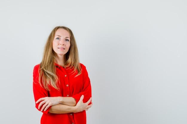 Mujer rubia de pie con los brazos cruzados en camisa roja y mirando confiado,