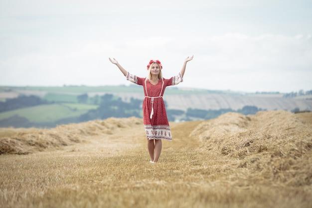 Mujer rubia de pie en el campo con los brazos abiertos