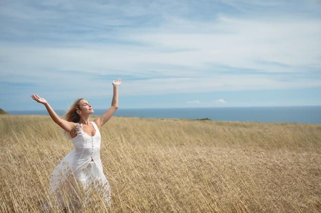 Mujer rubia de pie en el campo con los brazos alzados