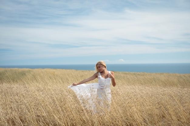 Mujer rubia de pie en el campo