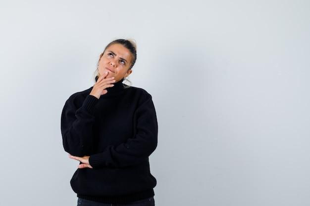 Mujer rubia de pie en pose de pensamiento en suéter negro y mirando sensible, vista frontal.
