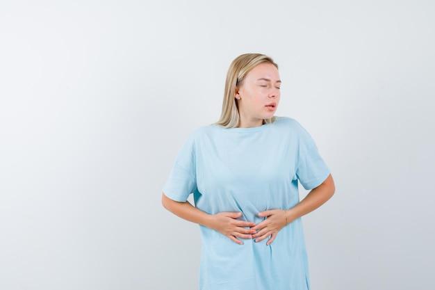 Mujer rubia poniendo las manos sobre el vientre, con dolor de estómago en camiseta azul