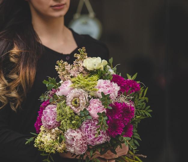 Mujer rubia poniendo ramo de flores decorativas naturales