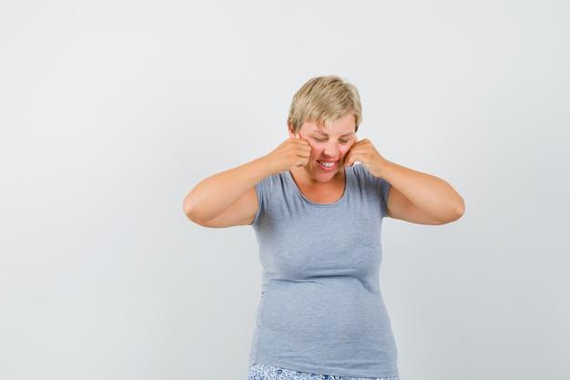 Mujer rubia poniendo sus manos en las mejillas y mirando hacia abajo en una camiseta azul claro y mirando sorprendido, vista frontal.