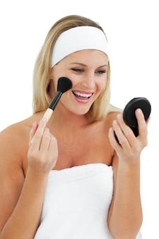 Mujer rubia poniéndose maquillaje