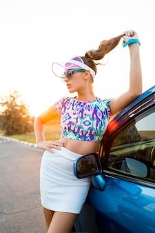Mujer rubia posando junto al coche con elegante traje de verano.