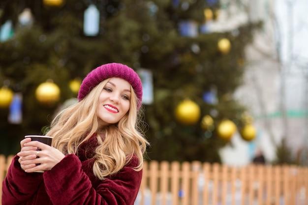 Mujer rubia positiva bebiendo café cerca del árbol de navidad en la plaza central de kiev