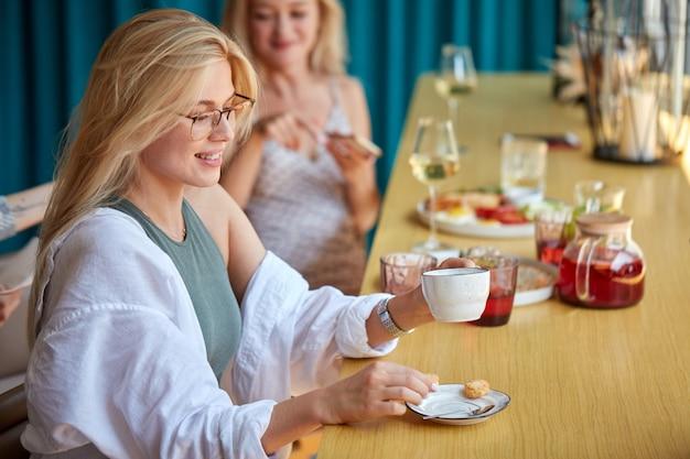Mujer rubia positiva tomando café en el restaurante