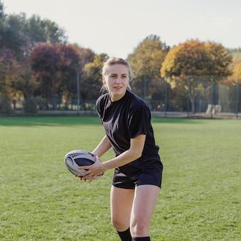 Mujer rubia preparándose para lanzar una pelota de rugby