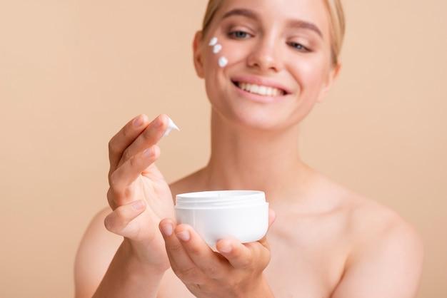 Mujer rubia de primer plano con crema para la cara y tarro